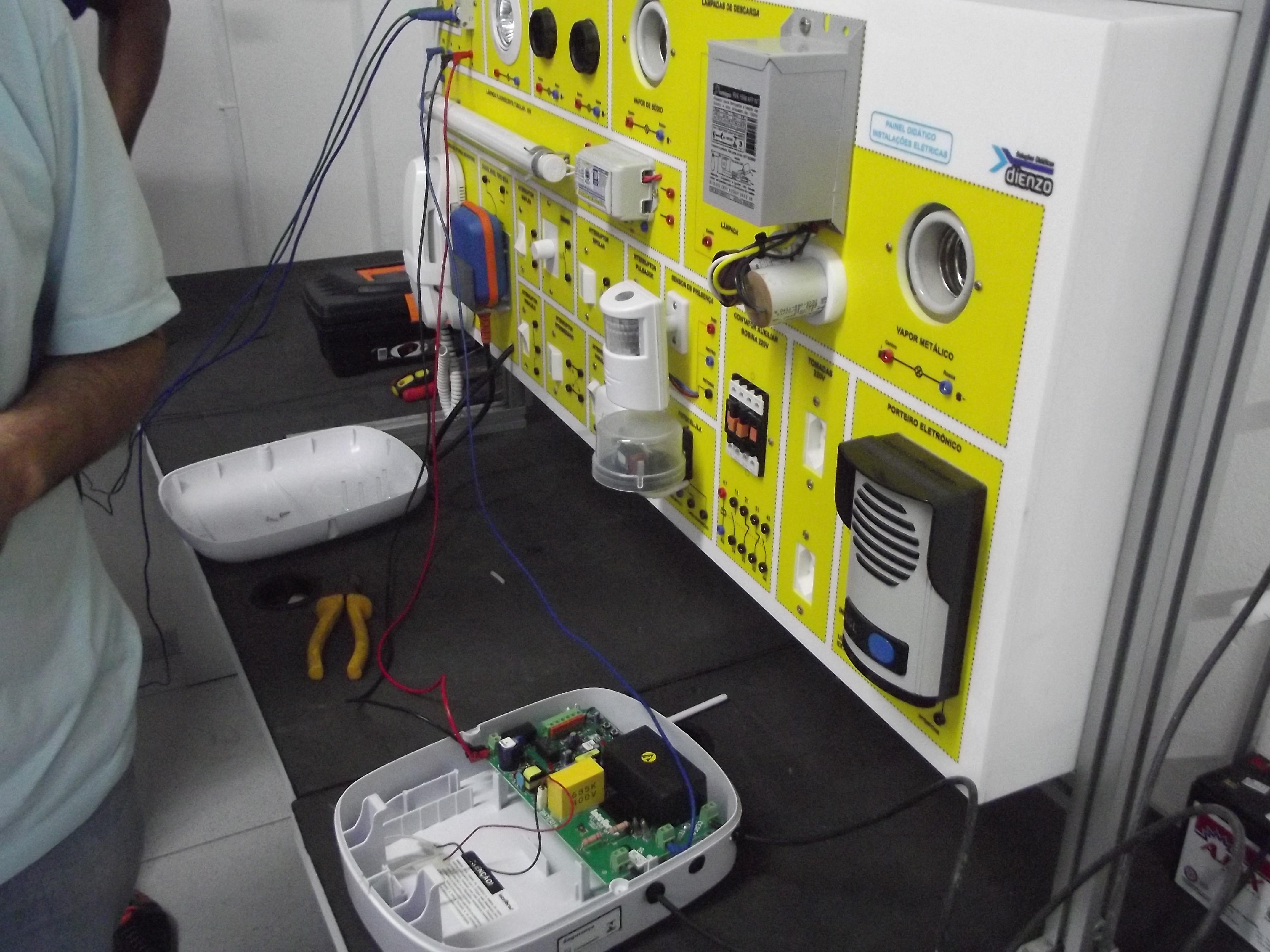 Aula prática no quadro de Instalações Elétricas